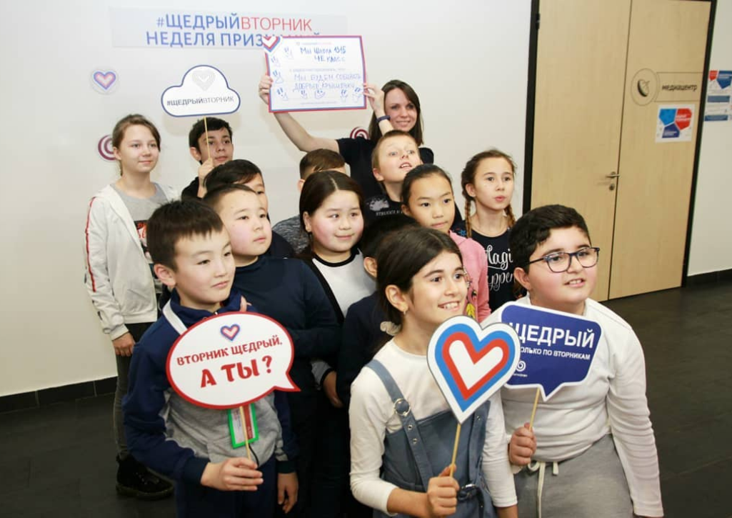 A group of children holding GivingTuesday Russia signs