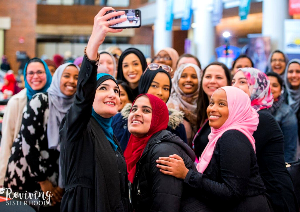 A group of women wearing hijab taking a selfie at a giving circle event