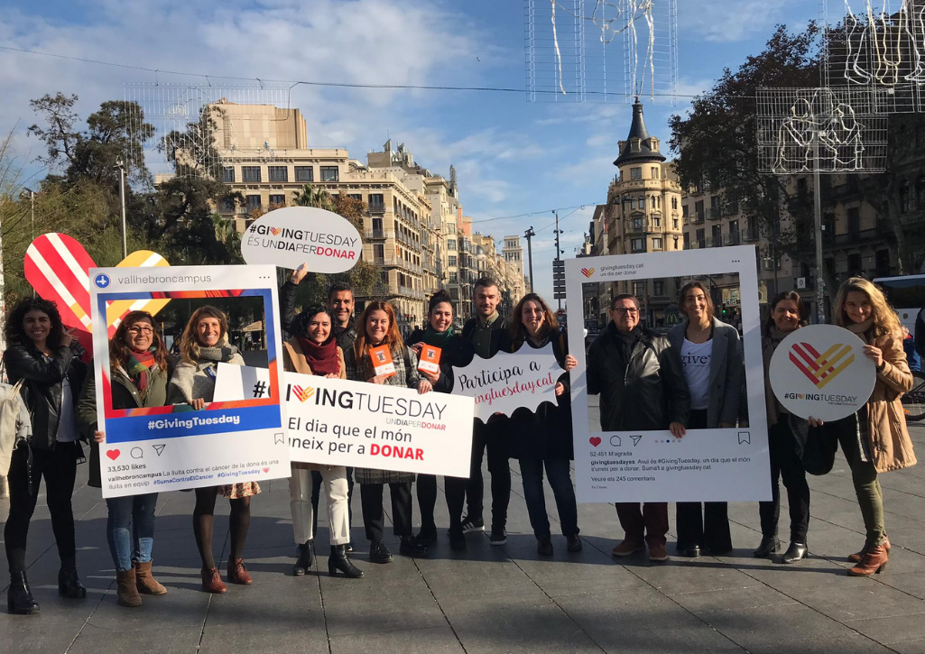 GivingTuesday Spain team celebrating on the street, holding Instagram selfie templates and posters