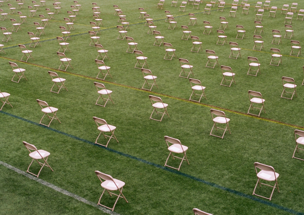 Rows of chairs outside on a green field of grass, separately 6 feet in all directions. The chairs are all empty.