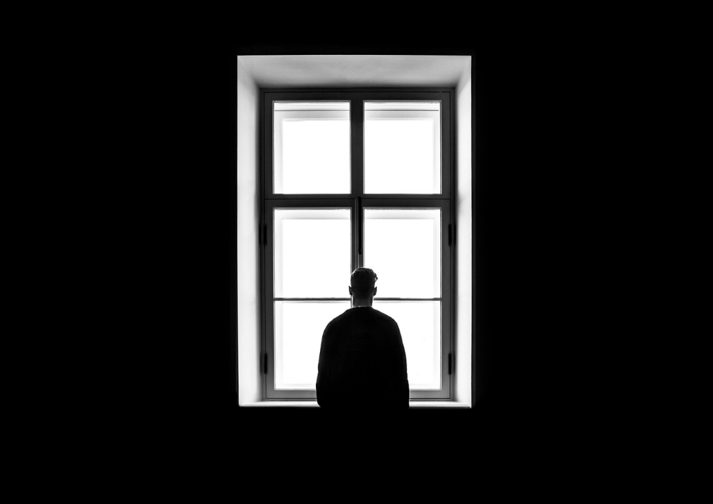 A silhouette of a man standing in a window
