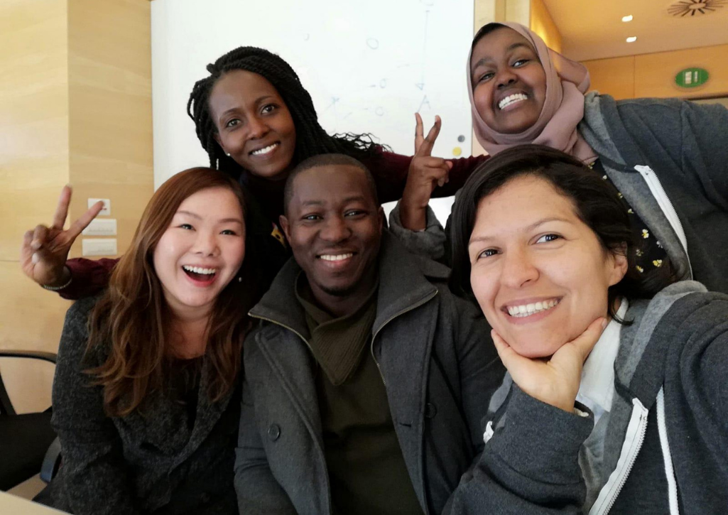 A group of GivingTuesday leaders smiling. Two are showing peace signs with their hands