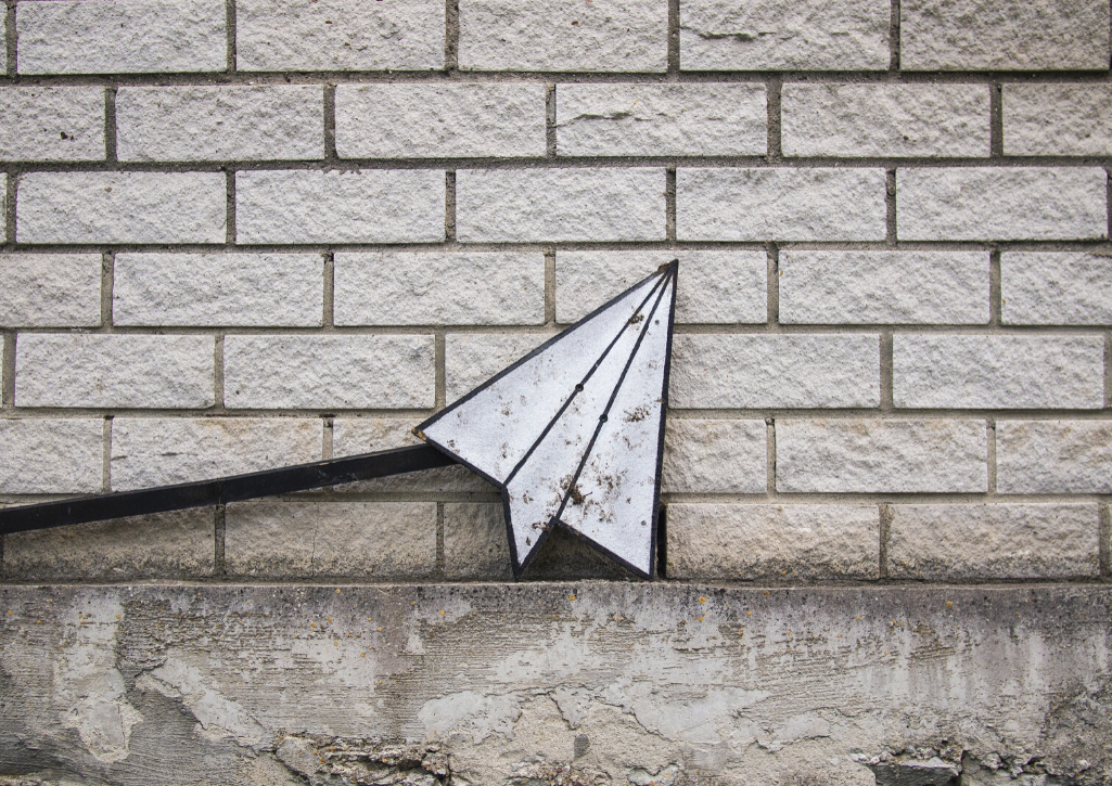 A paper airplane painting on a white brick wall