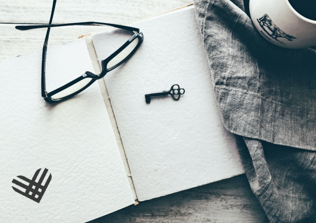 A sketchbook opened with a GivingTuesday logo drawn on it. Eyeglasses and a key are on top and a coffee mug to the left. The image is in black and white