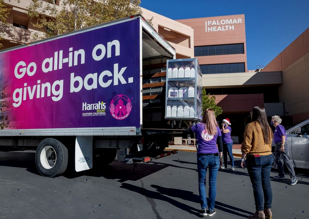"""People loading goods into a truck that says """"Go All In on Giving Back"""""""