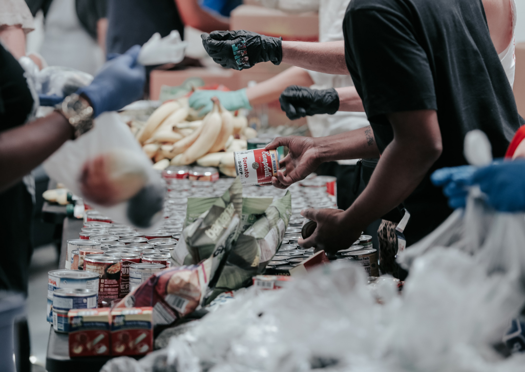 A close up shot of people wearing gloves, volunteering at the food pantry