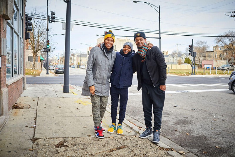 A family wearing GivingTuesday hats stands on a street corner in Chicago after handing out blessing bags to the homeless