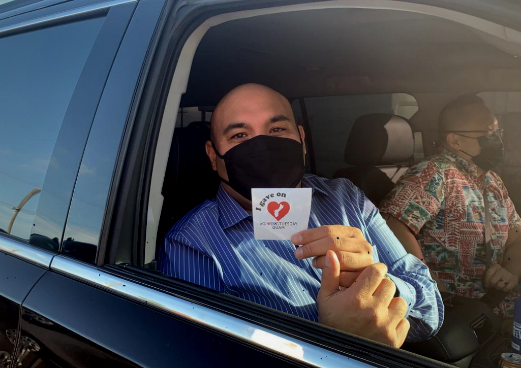 A man holding a GivingTuesday Guam sticker