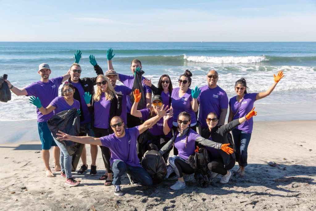 Harrahs Casino employees wearing purple shirts and posing with open arms on a beach that they've just cleaned up on GivingTuesday