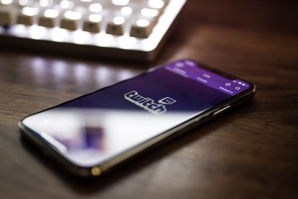 A phone with twitch open on a dark brown table.